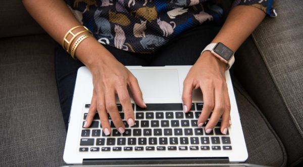 hands typing on a Mac keyboard. left hand has an Apple watch, right hand has two bracelets.