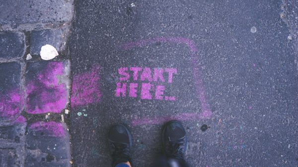 Looking down, you can see someone's feet, on concrete next to a purple spraypainted lettering that says 'Start Here'