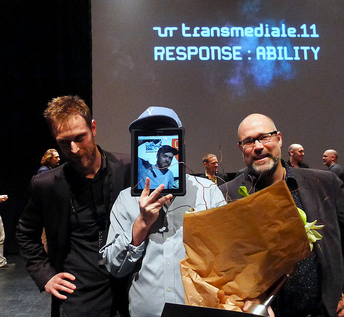 Jesse Scott (Graffiti Research Labs), center, accepts Open Web Award in Berlin on behalf of Evan Roth from Mark Surman and Henrik Moltke (Mozilla).