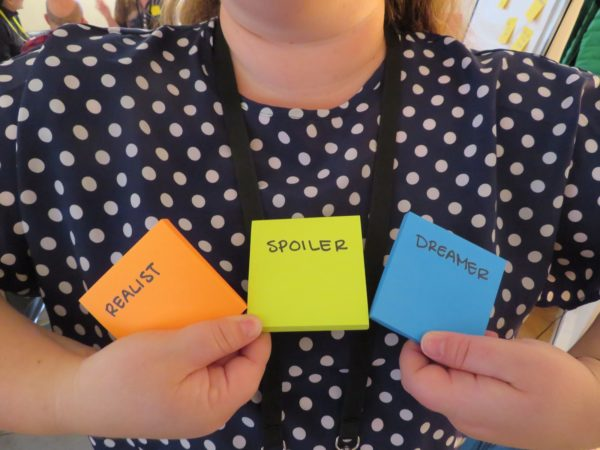 """A photo of a person holding 3 sticky notes in front of their body. The sticky notes read """"realist"""" """"spoiler"""" and """"dreamer"""" from left to right."""