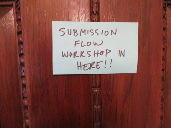 """Image: """"Submission flow workshop in here!!"""" posted on a sticky note on a wooden door."""