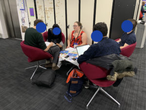 Jennifer crouching at a table with 4 participants in chairs. Participants are writing, speaking, and at their computers.